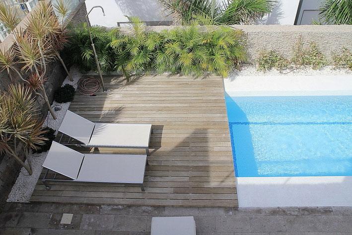 Blick auf die Sonnenterrasse am Pool vom Balkon aus.