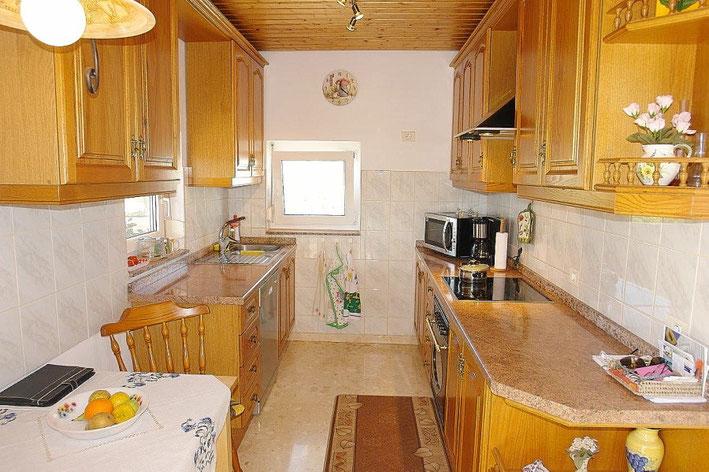 Blick in die Küche mit 2 Fenster und Platz für einen kleinen Esstisch.
