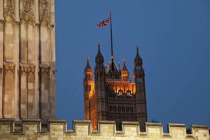 """Der Victoria Tower zur """"blauen Stunde"""". Im Vordergrund sind die Zinnen sowie ein Turm der Westminster Abbey zu sehen."""