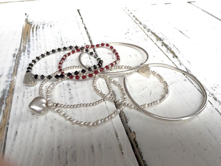 Diverse zilveren armbandjes mét of zonder pareltjes, gitjes of granaatjes, hartjes met of zonder tekst.