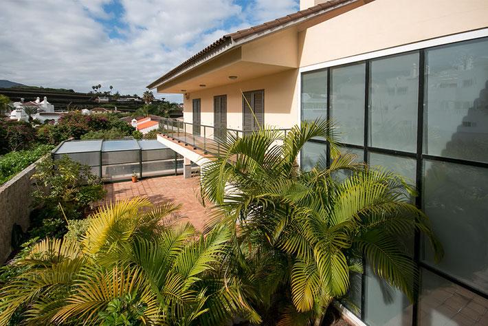 Villa Südseite mit verglaster Fassade, Terrasse und Blick zum Pool
