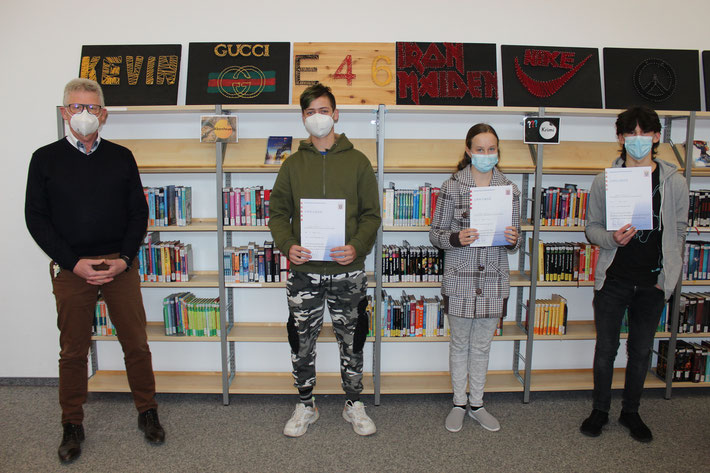 Mathesieger Tom Köhler, Elisa Göbel und Daniel Tremmel erhalten Urkunden und Gutscheine aus den Händen ihres Schulleiters Heiko Bickel.