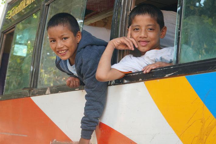 Kinder schauen aus Busfenster