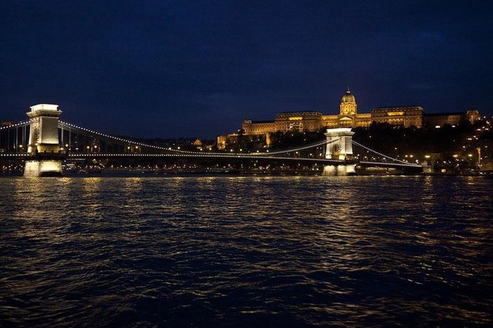 Panoramaaufnahme von der Stadthälfte Buda. Im Vordergrund ist die Kettenbrücke über die Donau zu sehen, im Hintergrund thront der Burgberg mit Palast.