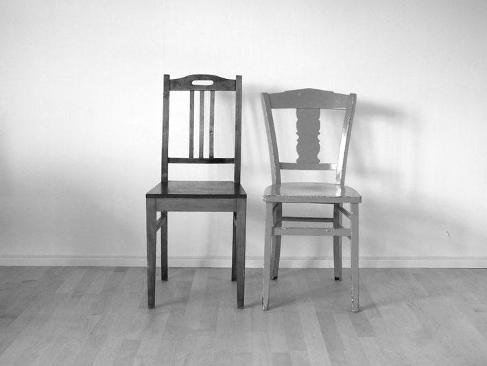 Zwei Stühle stehen nebeneinander und schauen einen an