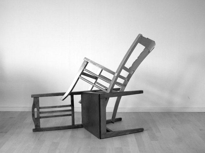 Zwei Stühle haben sich mit den Stuhlbeinen ineinander verhakt