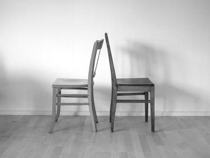 Zwei Stühle stehen Rücken an Rücken