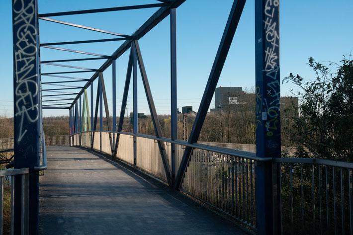 Eine Brücke über Bahnschienen führt von der Seite mit der Zeche Prosper zur Halde.