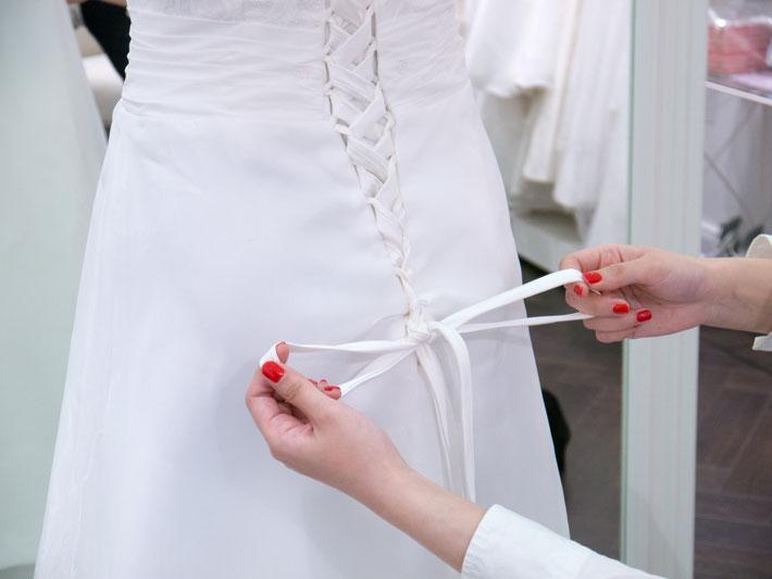 Audrey Brautmode Schleife binden am Brautkleid