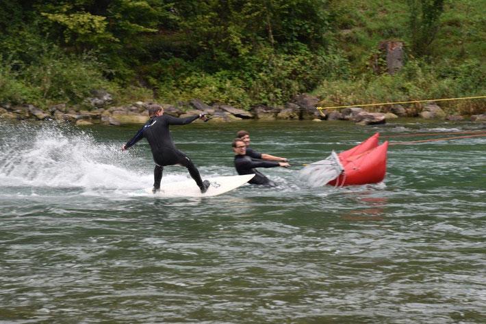 """Simon Gerber auf dem Surfbrett, im Hintergrund die Teamkollegen auf dem """"Segel"""""""