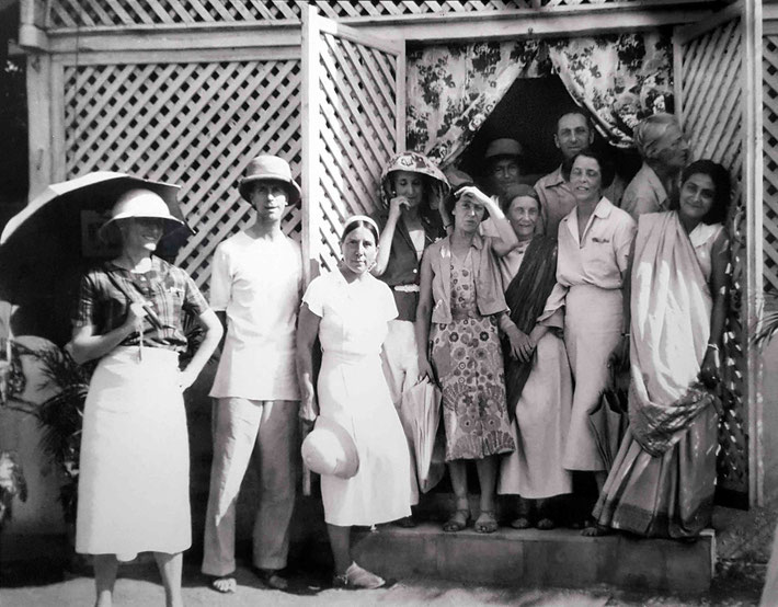 1938 : Nasik, India. Jean is standing on the first step, tall and in all-white clothing.