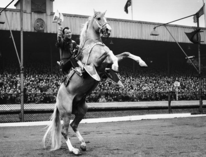 Roy Rogers, riding his horse Trigger in front of school children at Harringay Stadium, London, March 20, 1954