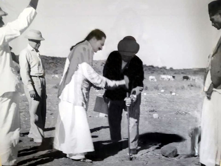 13th August 1939 : Meher Baba hammering a spike deep into the ground at the Central Point of the property. Papa Jessawala is holding the spike & Adi K. Irani wearing a plinth hat looking on.