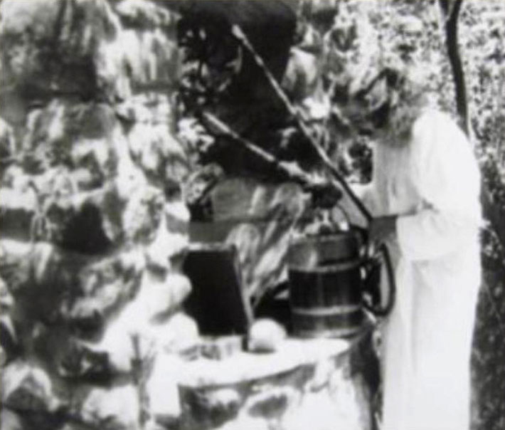 Meher Baba drawing water from the bucket at the well at Harmon