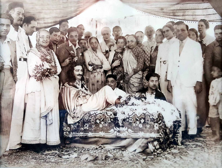 1937 - Nasik. Soonamasai is standing behind the two men seated behind Meher Baba, wearing a sari.