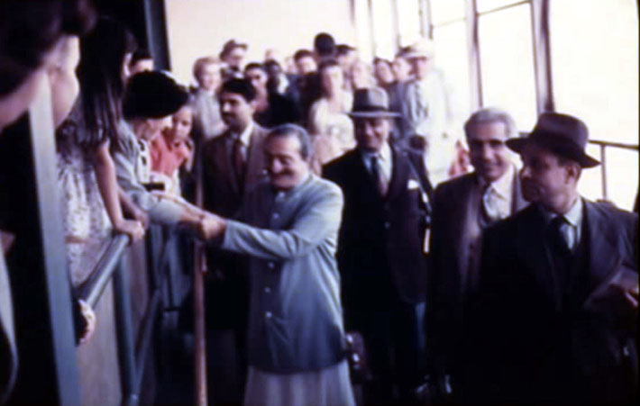 San Francisco Airport ; Baba possibly holding Kitty Davy's hands whilst walking to the plane along with the men mandali.