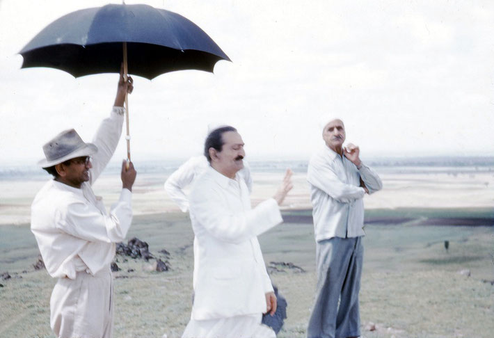 Kumar holding the umbrella for Meher Baba with Baidul looking on.