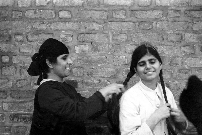 Gaimai Jessawala plaiting Manu's hair. Possibly Meherabad, late 1930's. Courtesy of the Jessawala Collection - AMB Archives, Meherabad, India.