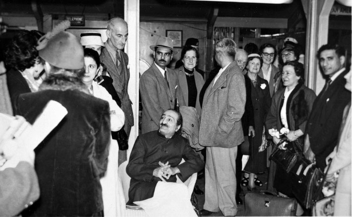1956 : Meher Baba with his men Mandali & his English followers at London Airport beofre departing for the USA.  Fred is standing behind Baba.