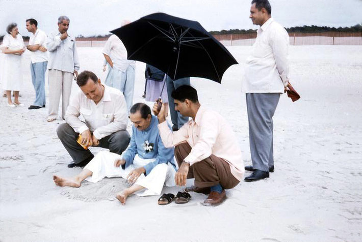 Meher Baba on Center Beach ( Arcadia Beach ) at Myrtle Beach, Sc. Eruch Jessawala holding the umbrella and Lud Dimpfl looking on.  Meherjee Karkaria standing behind.  Image captured by Anthony Zois from a film by Sufism Reoriented.