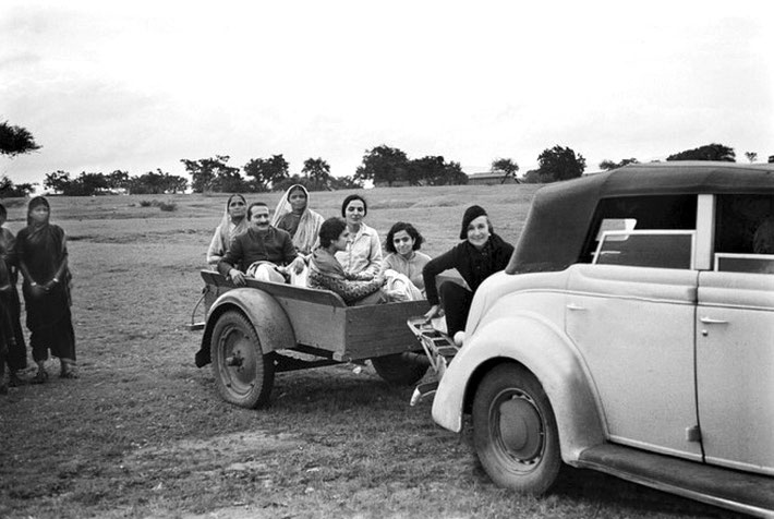 """Late 1930s - near Ahmednagar's Tower of Silence. Norina riding on Elizabeth's Ford V8 4-door convertable' s """"Dickie"""" seat. Baba and his women Mandali are riding on the trailer. Courtesy of MN Publ."""