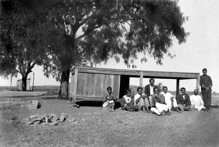 Meherabad Lower - Christmas 1927 : Meher Baba's Table Cabin with the Dhuni pit in the foreground. Some men Mandali are seated . Photo taken by Raosaheb.