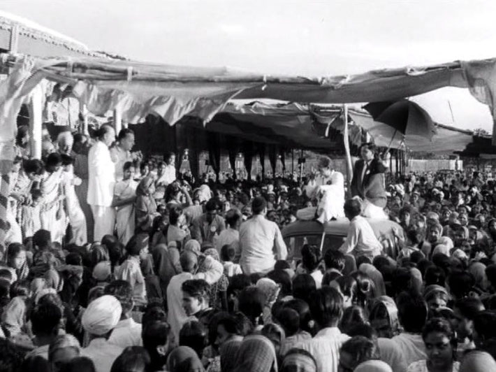 Ahmednagar, India ; 1954. Meher Baba atop of a car paraded through the crowds, whilst the Western men look on from the left of screen. LM p.4434