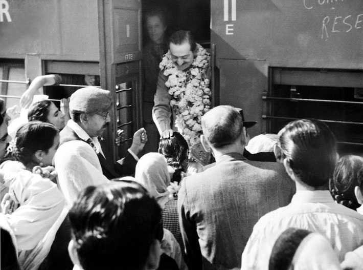 India ; Irene Conybeare standing beside Meher Baba whilst on a train trip. Baba is blessing a female follower. Courtesy of MN Publ.