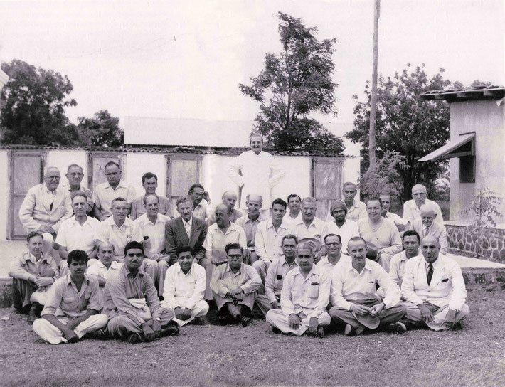 1954 - Upper Meherabad, India. Meher Baba with both his Eastern & Western followers. Malcolm is seated on the 2nd top row,far left. LM p.4500