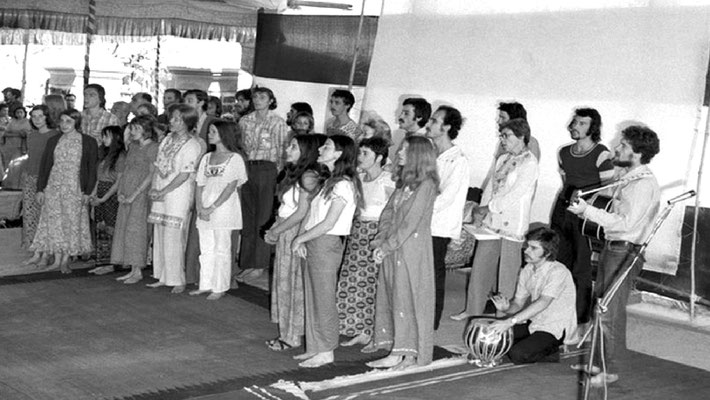 1973 Amartithi.  The Australian Meher Baba group singing at U.Meherabad during the celebrations.  May is on the far right wearing glasses. George McGahey sitting playing tabla is next to her.  Image courtesy of Raine Eastman-Gannett