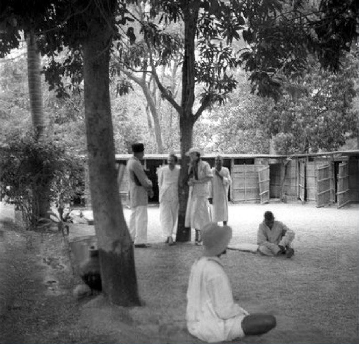Rahuri Mast Colony. Meher Baba leaning on tree with Norina Matchabelli listening to Abdulla Ramjoo