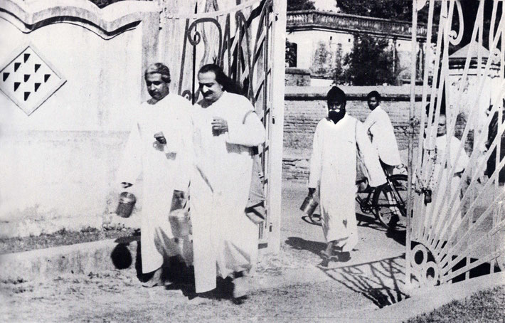 1949 - Baba begging in the New Life carry a satchel and Brass pot and accompanied by Adi K. Irani with Gustadji following.