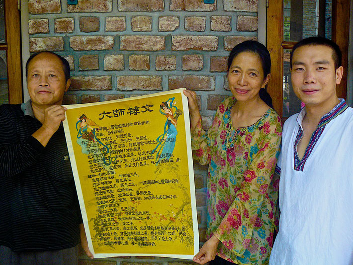 Meherabad, India - mid-2016 : Meher Baba's Master's Prayer in Chinese-Painted on silk paper by the artist Xie Guan on the left-Tian Gunther is in the center and Chen Shaubing is on the right. Photograph taken by Bil Sofer