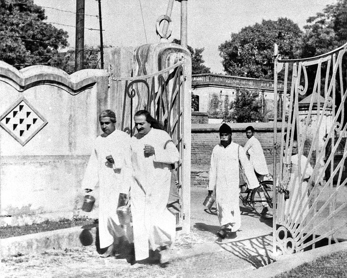 LP : 1949 - Baba begging in the New Life carry a satchel and brass pot and accompanied by Adi K. Irani with Gustadji following in Benares, India.
