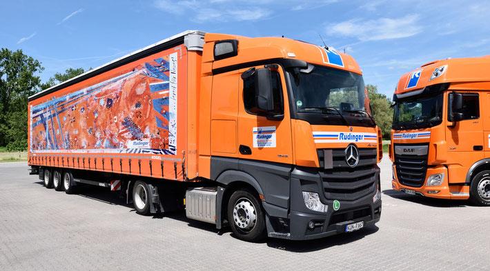 IM blauen Himmel stehen die Worte Maschinentransporte aus Leidenschaft. Man sieht weiße Wolcken und 2 LKW in orange fahren über eine Brücke. Vorne 1 kleiner, dahinter 1 LKW für Maschinentransporte.