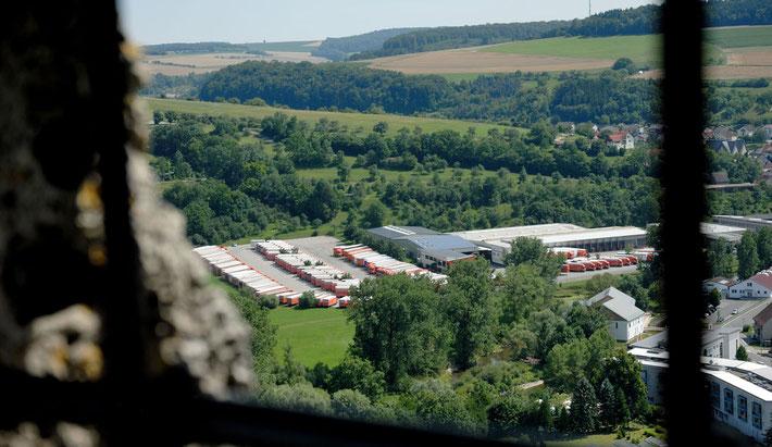 Man sieht vom Turm der Burg Krautheim auf die geordnete Reihe der LKW für den Maschinentransport. Ein Maschinentransporter neben dem anderen. Vorne sieht man durch das alte Gitter des Turmfensters.