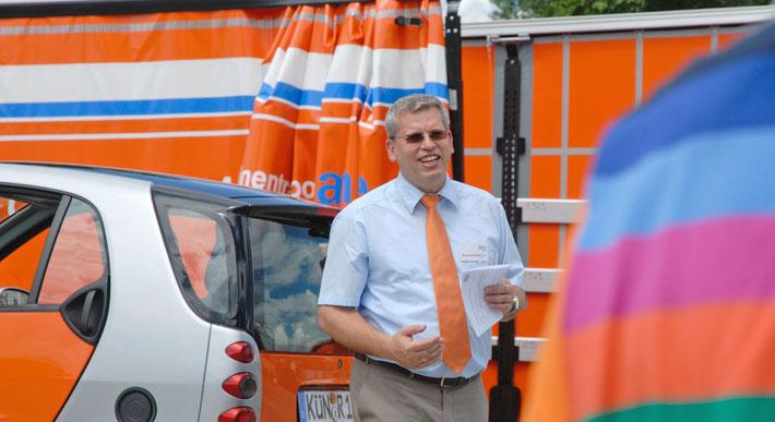 In großen weißen Lettern liest man im Bild Maschinentransporte aus Leidenschaft. Im Bild sieht man den Inhaber der Spedition, er spricht zur Kamera und steht vor 2 Fahrzeugen in Orange.