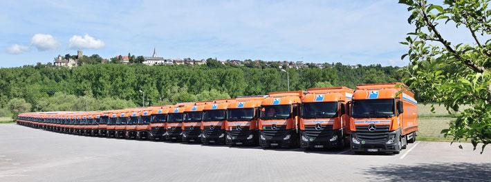 Zum Thema Maschinentrnasport sieht man auf eine Reihe von LKW einer Spedition. Es sind etwa 20 parallele vor blauem Himmel. Rechts hinten sind grüne Bäume