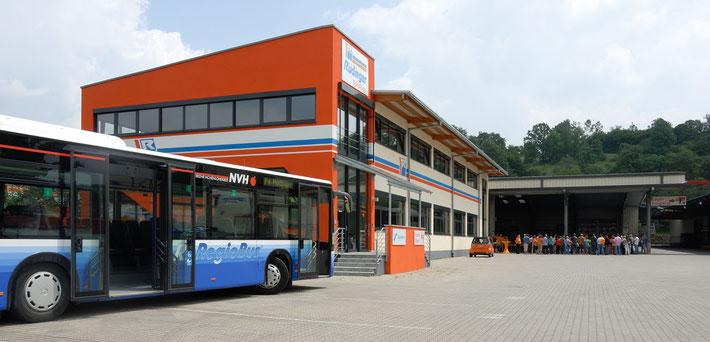 Man sieht links einen blauen Gelenkbus mit offenen Türen. Rechts daneben ist das neue Verwaltungsgebäude in orange/blau/weiß und rechts sieht man die Langguthalle mit vielen Menschen, die dort sitzen.