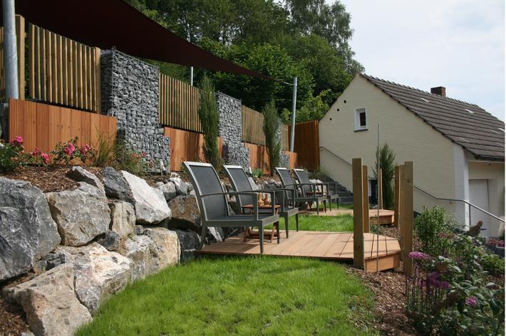 Garten mit einer Holzterrasse und einem Holzzaun