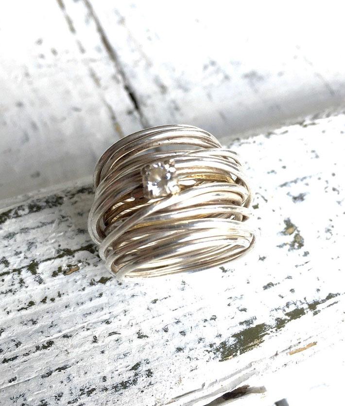 Trapped for life, zilveren draadring met daarin een verlovingsring gestoken.