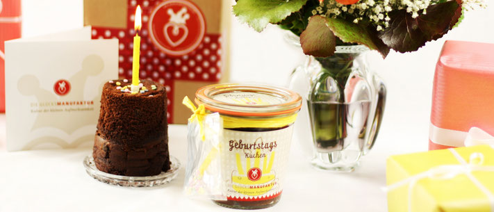 Geburstags-Kuchen im Glas mit Karte und Kerze auf Geburtstagstisch