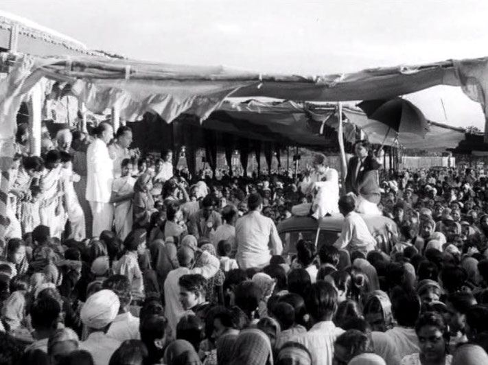 Ahmednagar, India ; 1954. Meher Baba atop of a car paraded through the crowds, whilst the Western men look on from the left of screen