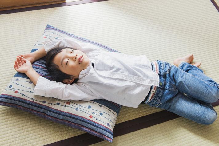 畳の上で昼寝をする子供