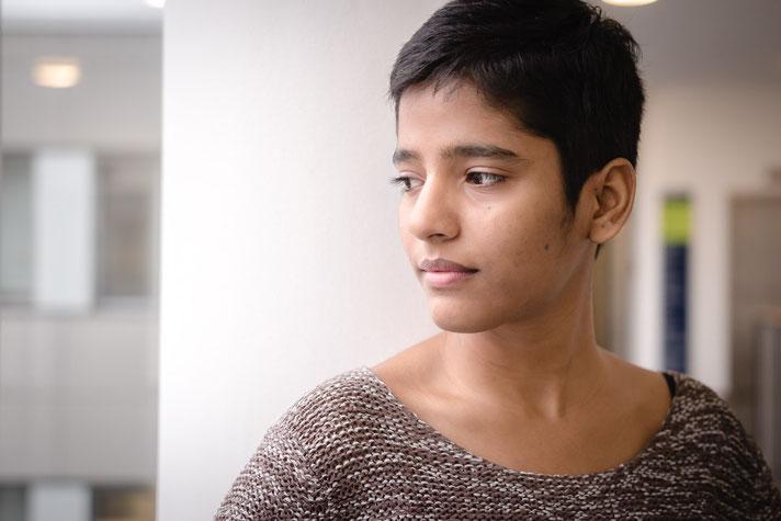 Ruhiges Bild einer jungen Frau die den Blick abwendet vor einer Säule