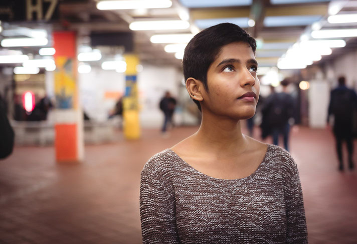 Eine junge Frau steht inmitten von anderen Menschen in der Universität Erlangen