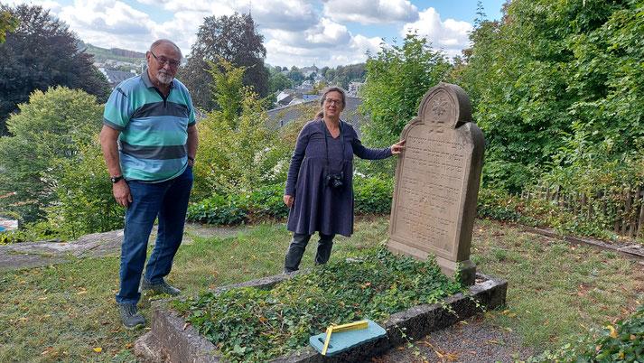 Zwei Personen neben einer Grabstelle