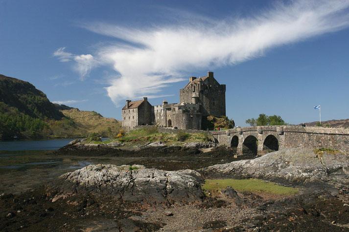 Eilean Donan Castle im Sonnenschein mit weißer Federwolke darüber. Eine Steinbrücke führt zur Schlossruine.