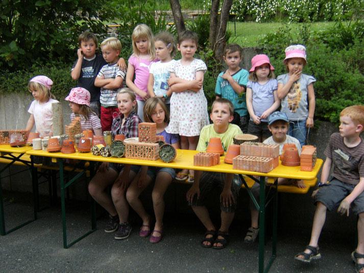 Stolze Handwerker und Künstler mit den fertigen Insektennisthilfen und Ohrwurm-Hotels.
