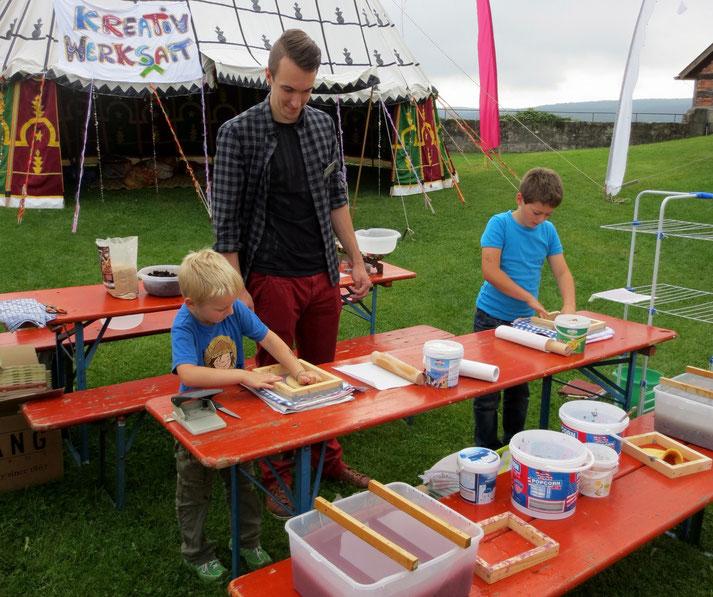 """Mein Sohn Christoph, der """"Papierschöpf-Meister"""" bei einer unserer Rosenmesse-Kinder-Aktionen (auf dem Tisch dahinter ist die Samenbomben-Werkstatt zu erkennen)."""